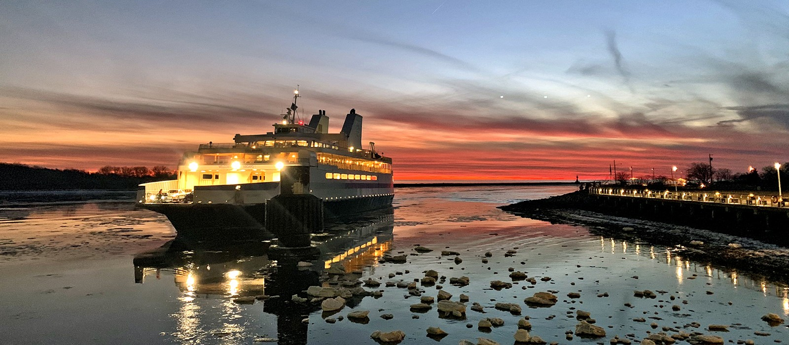 The Cape May-Lewes Ferry arrives on an icy bay with a beautiful red sky and sunset in the background