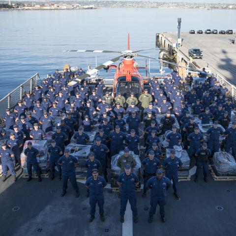 United States Coast Guard at attention on deck of rescue vessel with USCG helicopter
