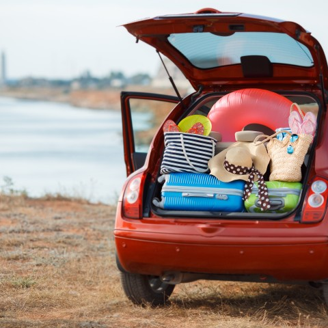 red car at beach packed with luggage and beach paraphernalia